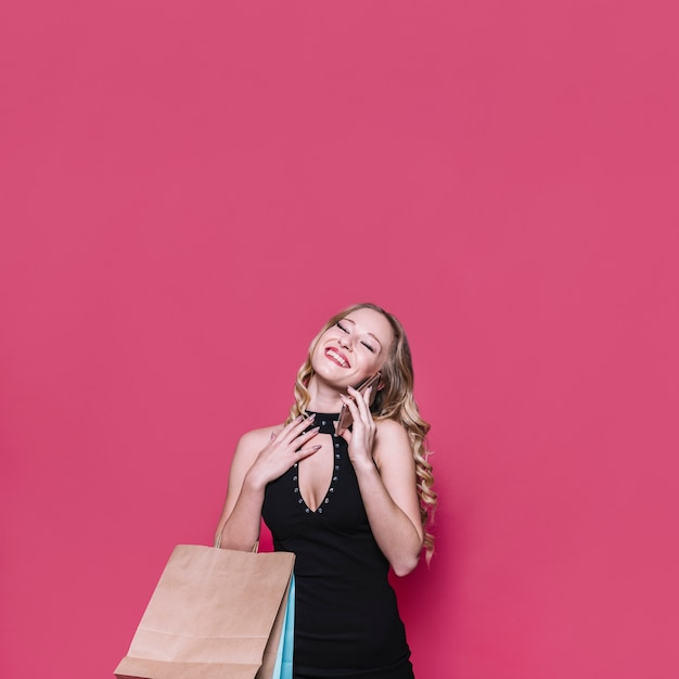 Femme blonde joyeuse avec des sacs parlant au téléphone Photo gratuit
