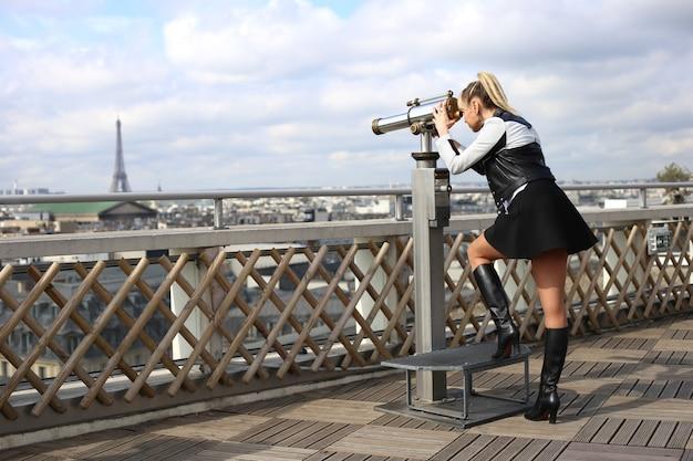 Une Femme Blonde Avec De Longues Jambes Dans Une Jupe Courte Regarde à Travers Un Télescope à La Tour Eiffel Photo Premium
