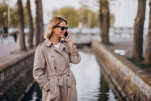 Femme blonde en manteau à l'extérieur dans le parc à l'aide de téléphone Photo gratuit