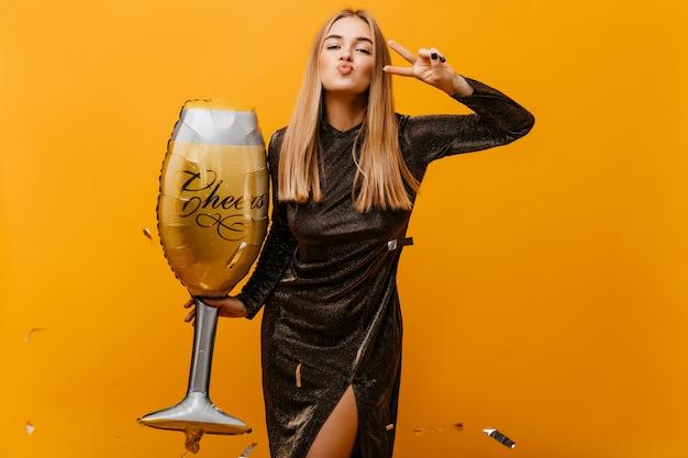 Femme Blonde Positive Posant Avec Un Grand Verre à Vin. Adorable Femme Blanche En Robe Préparant La Fête D'anniversaire. Photo gratuit