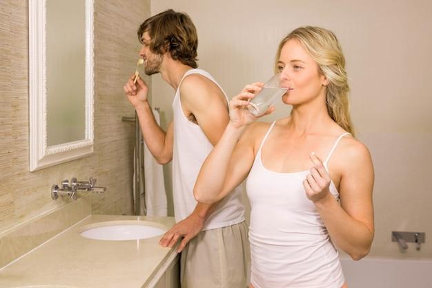 Femme blonde prenant une pilule avec son petit ami se brosser les dents dans la salle de bain à la maison Photo Premium