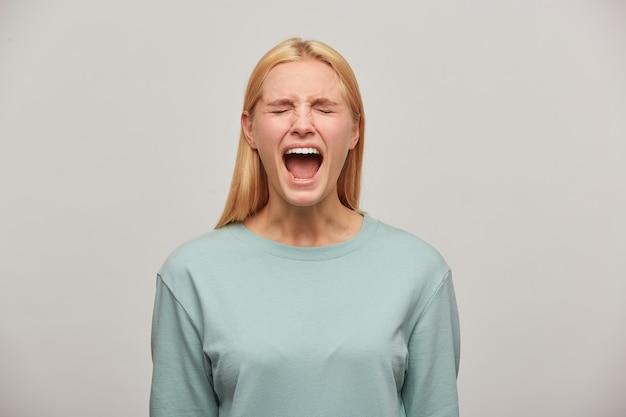 Femme Blonde Qui Crie A L'air Effrayée Peur Imiter Cri Cri, émettre Un Appel Fort Ou Pleurer Photo gratuit