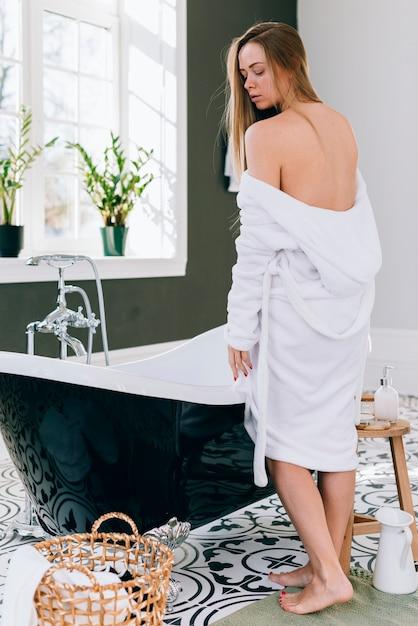 Femme blonde qui pose dans la salle de bain avec un peignoir Photo gratuit