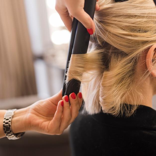 Femme blonde se bouclant les cheveux Photo gratuit