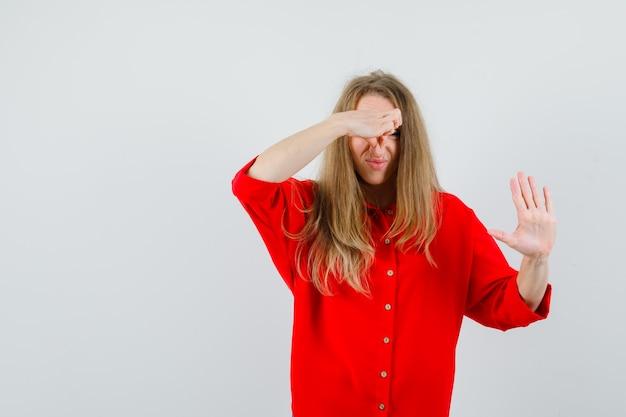 Femme Blonde Se Pincer Le Nez En Raison D'une Mauvaise Odeur En Chemise Rouge Et à La Dégoût. Photo gratuit