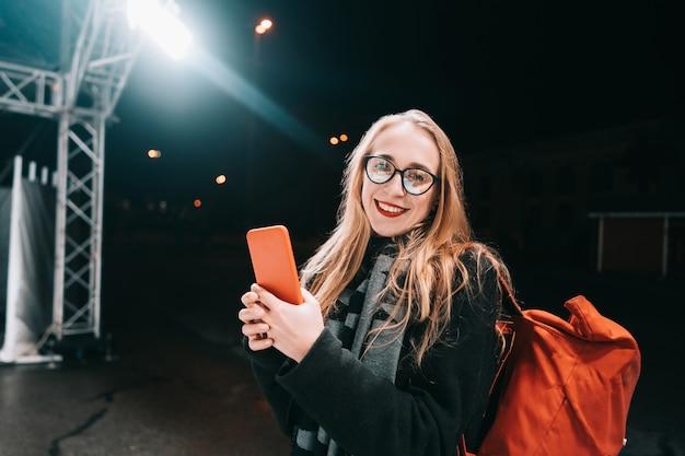 Femme Blonde Avec Un Smartphone Dans La Nuit Dans La Rue. Photo gratuit