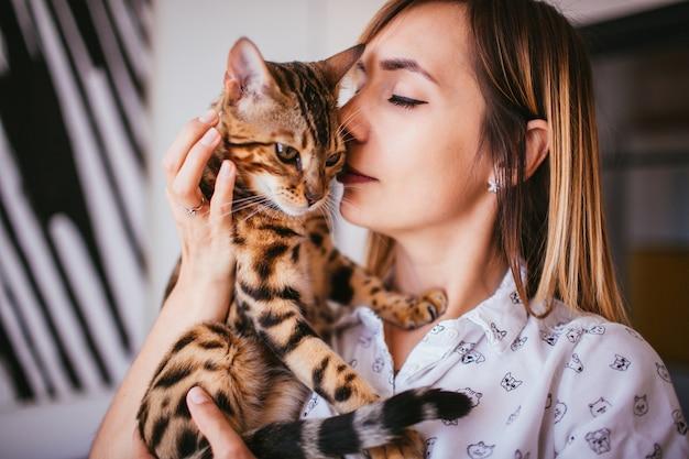 Femme blonde tient un chat bengal Photo gratuit