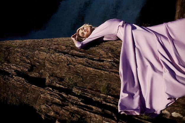 Femme Blonde Vêtue D'une Longue Robe Rose Se Trouvant Sur Une Pierre Photo Premium