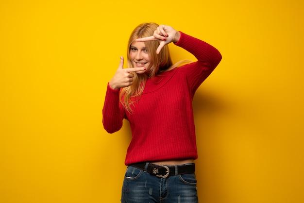 Femme blonde sur le visage de mur jaune. symbole d'encadrement Photo Premium