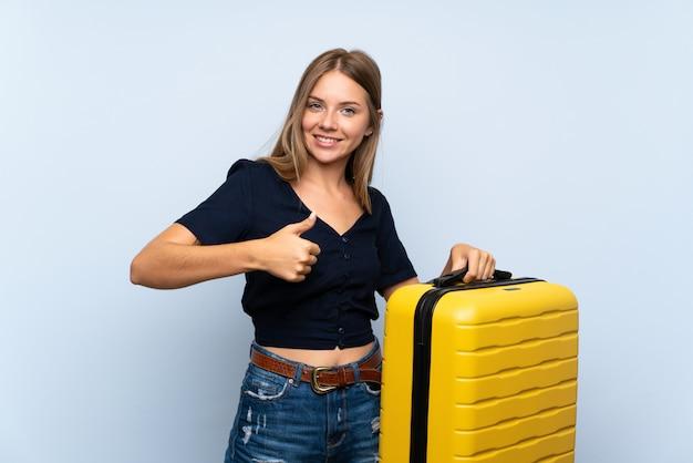 Femme blonde voyageur avec valise avec le pouce levé parce que quelque chose de bien est arrivé Photo Premium