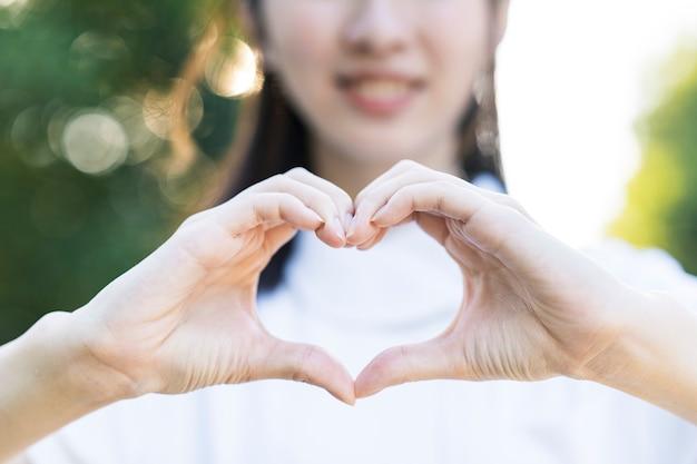 Une Femme En Blouse Blanche En Forme De Coeur Avec Les Deux Mains Photo Premium