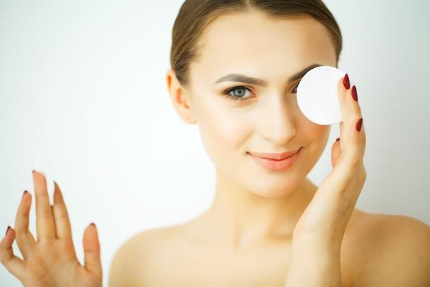 Femme en bonne santé avec des tampons de coton blancs. concept de traitement hygiénique, nettoyant et facial Photo Premium