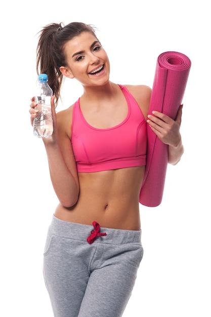 Femme En Bonne Santé Tenant Une Bouteille D'eau Minérale Et Tapis D'exercice Photo gratuit