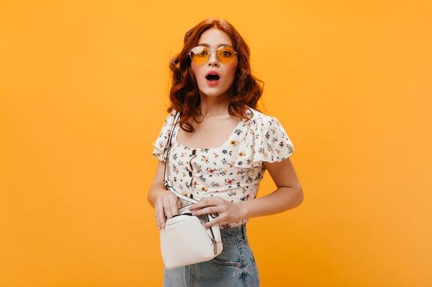 Femme Bouclée à Lunettes De Soleil Regarde Confusément La Caméra Et Tient Un Petit Sac Blanc. Photo gratuit