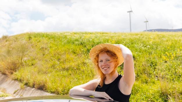 Femme bouclée rousse souriante dans la nature Photo gratuit