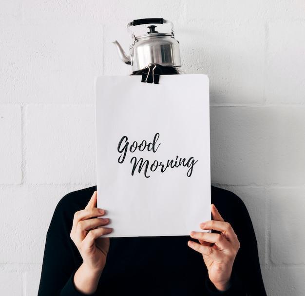 Femme, bouilloire, tête, bon matin, message, papier, tenue, devant, figure, contre, mur blanc Photo gratuit