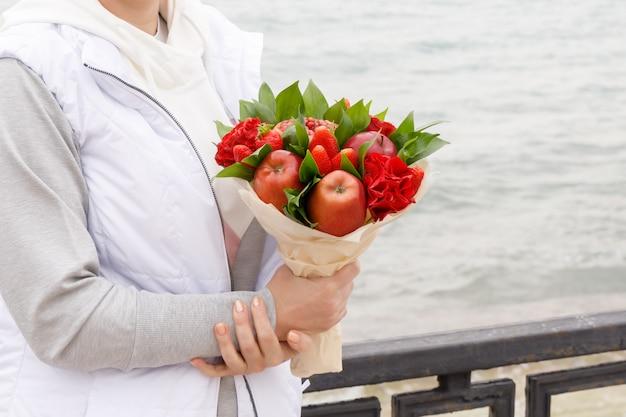 Femme avec un bouquet de fleurs et de fruits se dresse sur le quai en automne Photo Premium