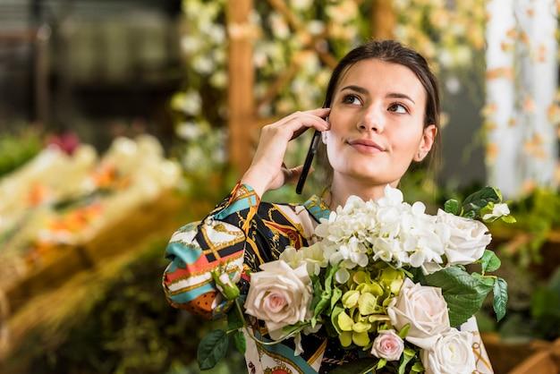 Femme avec bouquet de fleurs parler par téléphone Photo gratuit