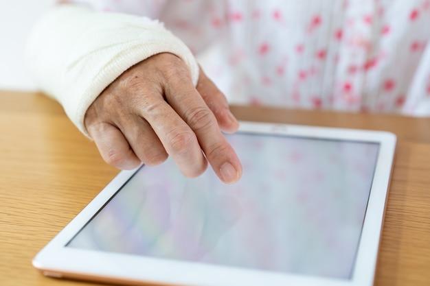 Femme Bras Blessé Lisant Un E-book Sur La Tablette Se Bouchent. Soins De Santé Et Bien-être Dans Le Concept De Société Vieillissante. Photo Premium