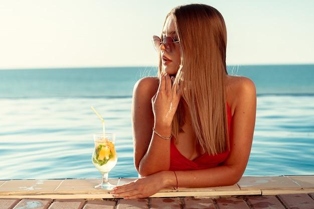 Femme Bronzée En Bikini Rouge Dans Une Piscine Avec Cocktail Photo Premium