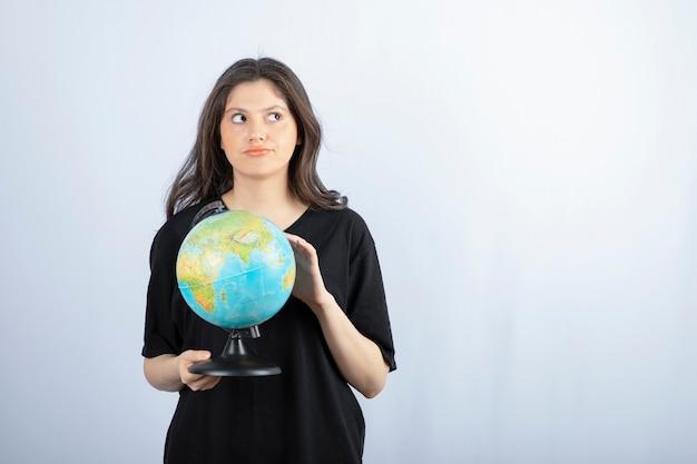 Femme Brune Aux Cheveux Longs Choisit Un Endroit Pour Voyager Sur Le Globe. Photo gratuit