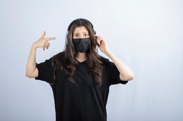 Femme Brune Aux Cheveux Longs Dans Un Masque Médical Pointant Sur Les écouteurs. Photo gratuit
