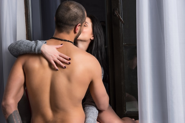 Femme Brune Dans Une Robe Tricotée Est Assise Sur Le Rebord De La Fenêtre Et Embrasse Son Mari Avec La Poitrine Nue Et Les Mains Tatouées Photo Premium