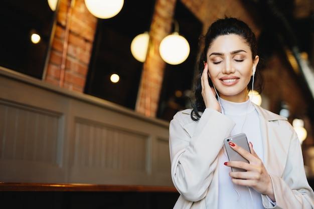 Femme brune reposante avec une belle apparence, fermant les yeux de joie tout en écoutant de la musique à fond dans ses écouteurs Photo Premium