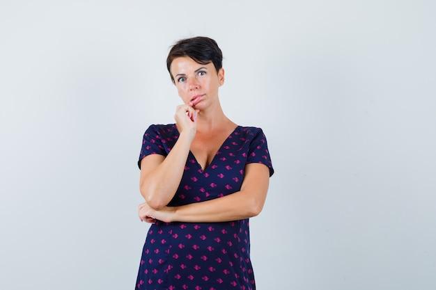 Femme Brune En Robe à Motifs Violets Et Rouges Tenant Ses Doigts Près De Sa Bouche Et Penser à Quelque Chose Et à La Vue Pensive, Vue De Face. Photo gratuit