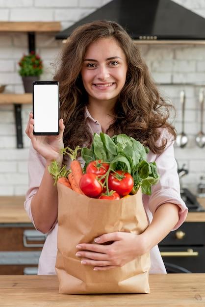 Femme brune avec un sac en papier rempli d'aliments sains Photo gratuit