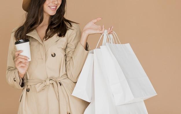 Femme brune avec des sacs à provisions et café Photo gratuit