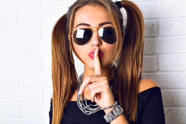 Femme Brune Sexy Posant Au Mur De Briques Urbaines. Bouchent Le Portrait De Mode, Met Le Doigt Sur Ses Lèvres Et Dis Chut Photo gratuit