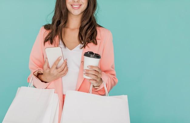Femme brune avec smartphone et café Photo gratuit