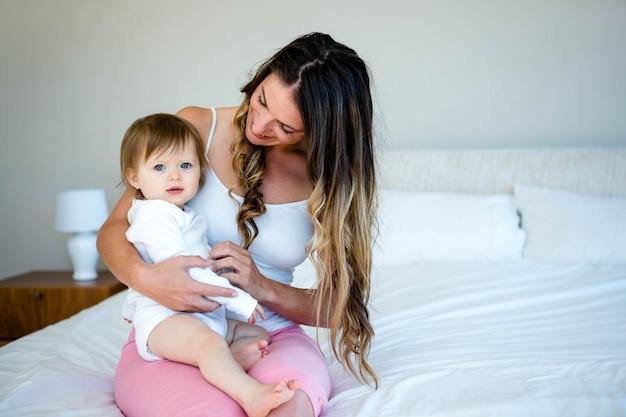Femme brune souriante tient un joli bébé sur un lit Photo Premium