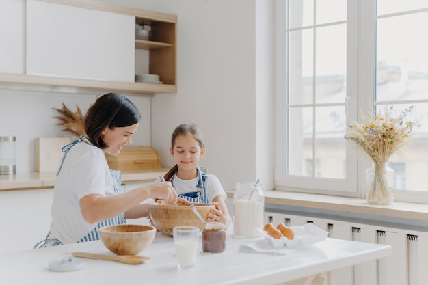 Femme Brune Avec Sourire Montre à Sa Petite Fille Comment Cuisiner Photo Premium