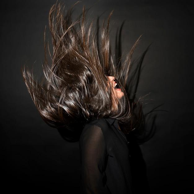 Femme brune en tenue de soirée avec des cheveux venteux Photo gratuit