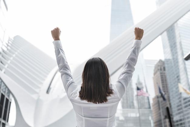 Femme brune vue arrière exprimant la victoire Photo gratuit