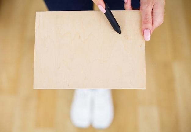 Femme de bureau mains tenant un arbre conseil sur fond blanc. copyspace. place pour le texte Photo Premium