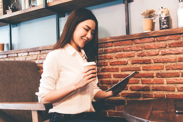 Femme buvant du café et travaille sur une tablette au café Photo Premium