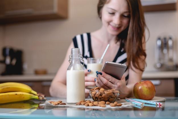 Femme buvant du lait d'amande biologique tenant un téléphone à la main dans la cuisine. produit végétarien sain Photo Premium