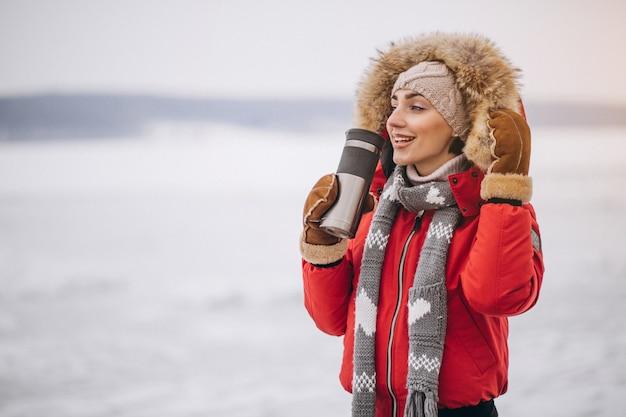 Femme buvant du thé chaud en hiver à l'extérieur Photo gratuit