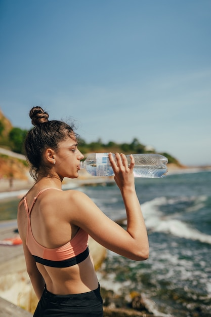 Femme Buvant De L'eau Fraîche à Partir D'une Bouteille Après L'exercice Sur La Plage Photo gratuit