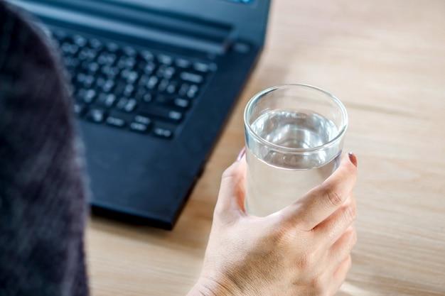 Femme buvant de l'eau tout en travaillant sur ordinateur Photo Premium