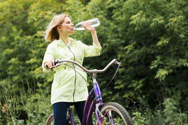 Femme buvant de l'eau à vélo Photo gratuit