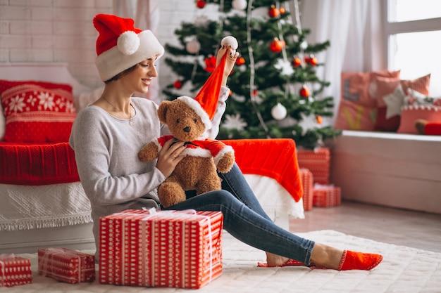 Femme avec des cadeaux de noël par sapin de noël Photo gratuit