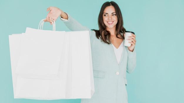 Femme avec café et sacs à provisions sur fond bleu Photo gratuit
