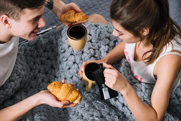Femme, café verser, dans tasse, sur, lit Photo gratuit