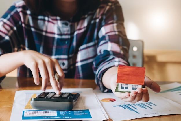 Femme calculant son budget avant de signer un contrat de projet immobilier Photo Premium