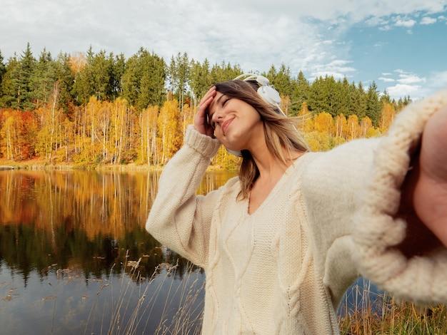Femme avec un casque près du lac en automne Photo Premium