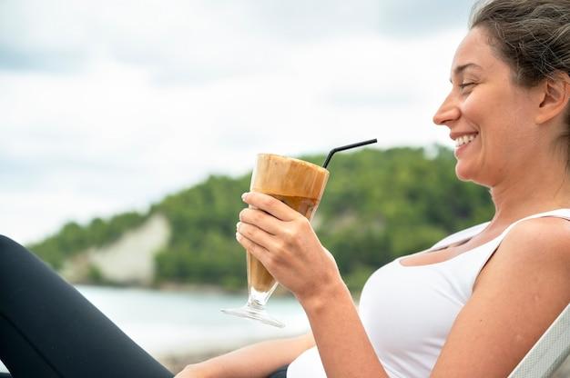 Femme Caucasienne Souriante Tenant Un Verre De Café Sur Une Plage Avec De La Mousse Et De La Paille Avec Des Collines Photo gratuit